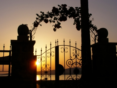 An ornamental gate along the waterfront frames the sunset in Ayvalik.