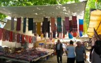 At the main Thursday market in Ayvalik colorful fabrics hand from the shade awnings strung between buildings.